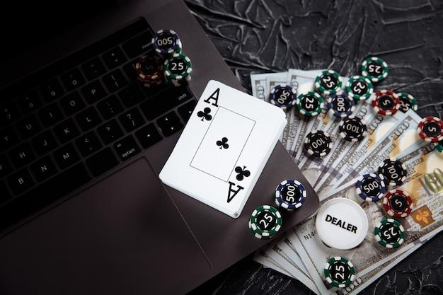 Carte da poker e pile di fiches da poker su un computer portatile. concetto online di poker.