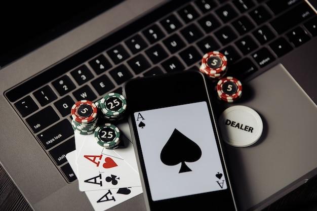 Fiches da poker, carte e smartphone su una tastiera grigia. concetto online di poker