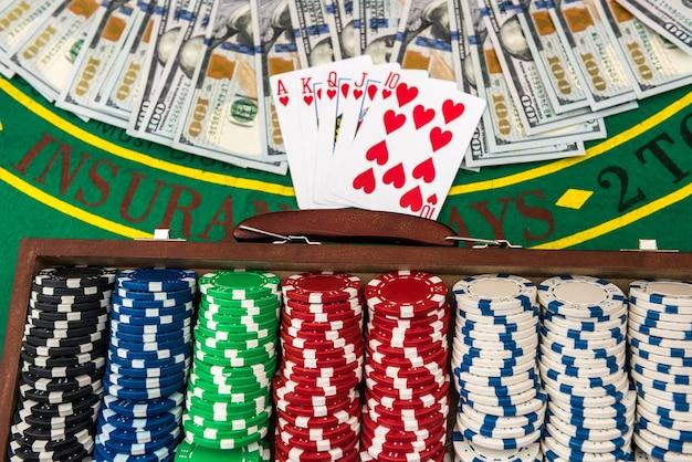 Poker chips nel caso su un tavolo da gioco con carte e dollari