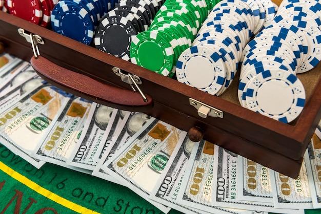 Fiches da poker e dollari in un caso sul tavolo da gioco.