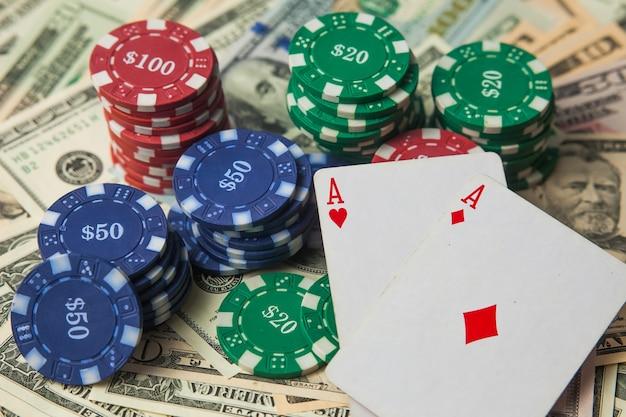 Chip di poker su dollari e due assi