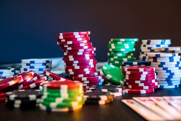 Fiches da poker e carte da gioco sul tavolo nero.