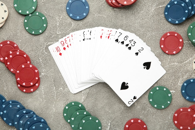 Fiches da poker e carte da gioco sul muro grigio. casinò