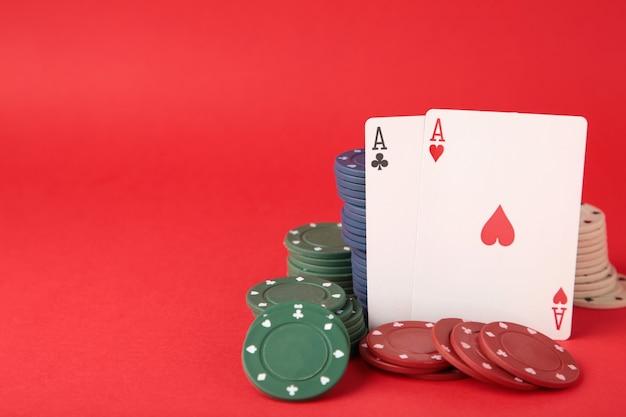 Fiches da poker e carte da gioco sulla parete rossa. casinò