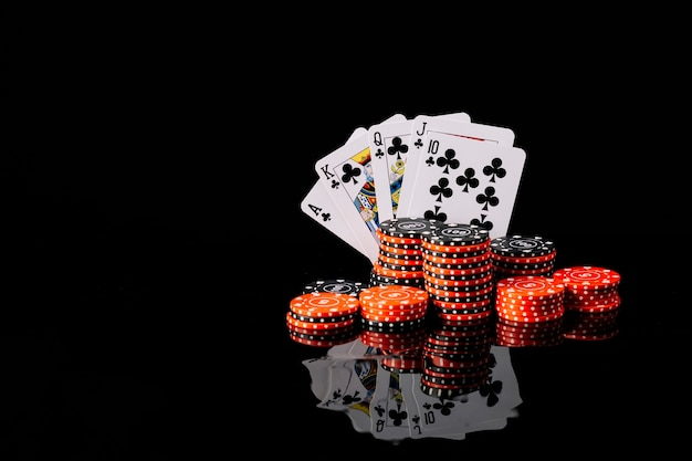 Poker chips e royal flush club su sfondo nero riflettente