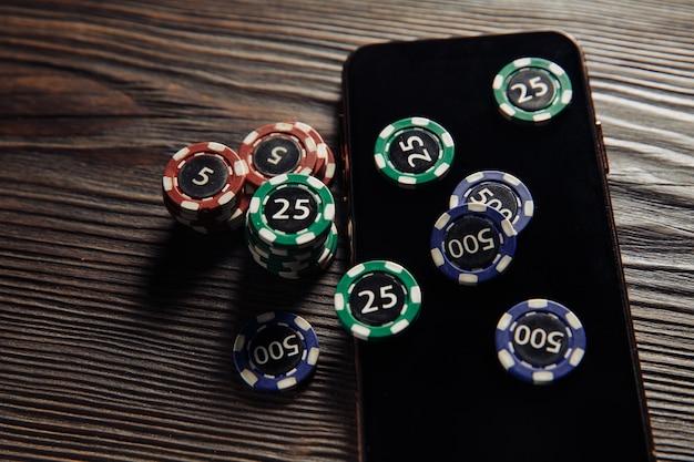 Fiches da poker e smartphone su un tavolo di legno