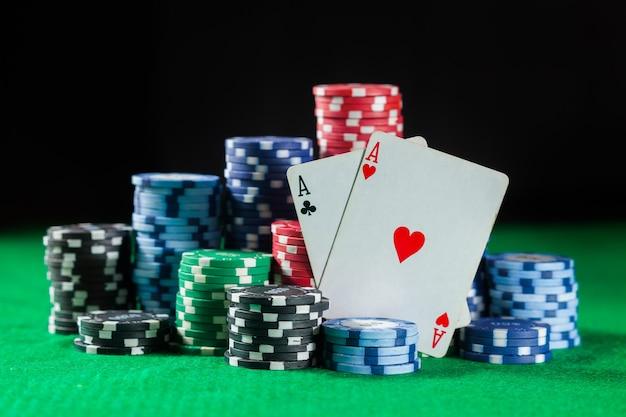 Le fiches da poker si impilano con due carte un asso. sul tavolo verde su una superficie nera e scura.