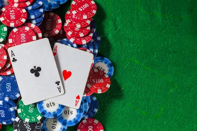 Le fiches da poker si impilano con due carte un asso. sul tavolo verde