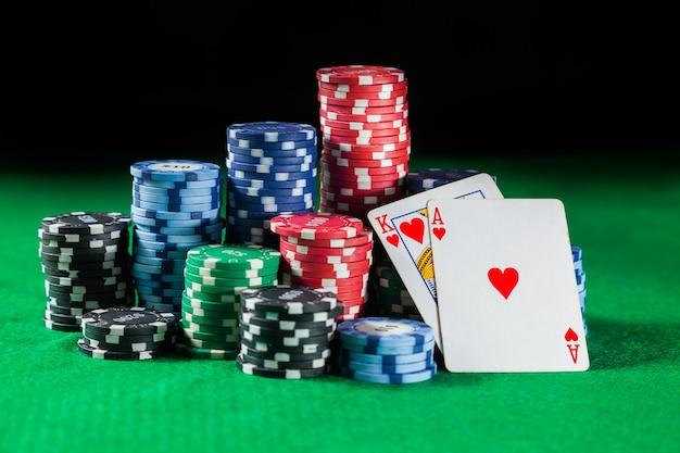 Le fiches da poker si impilano con due carte re e ace. su una superficie verde.