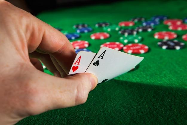 Fiches da poker con due assi sulla superficie verde.