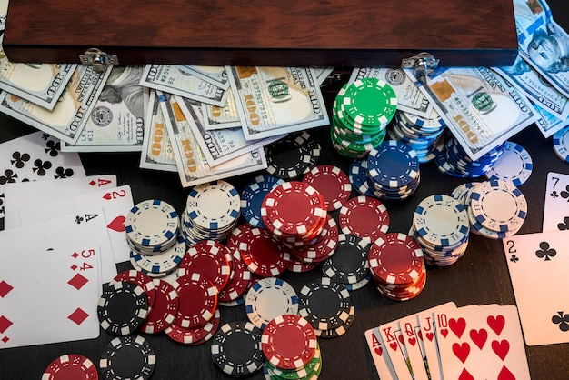 Combinazione di poker: fiches e denaro sul tavolo nero.