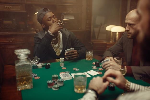 Giocatori di poker al tavolo da gioco con panno verde