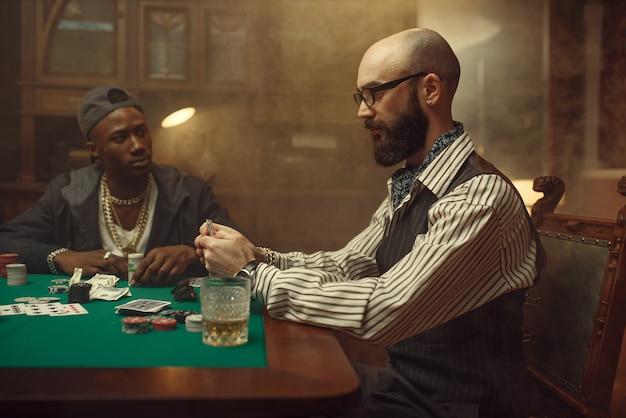 I giocatori di poker piazzano scommesse in denaro sul tavolo da gioco
