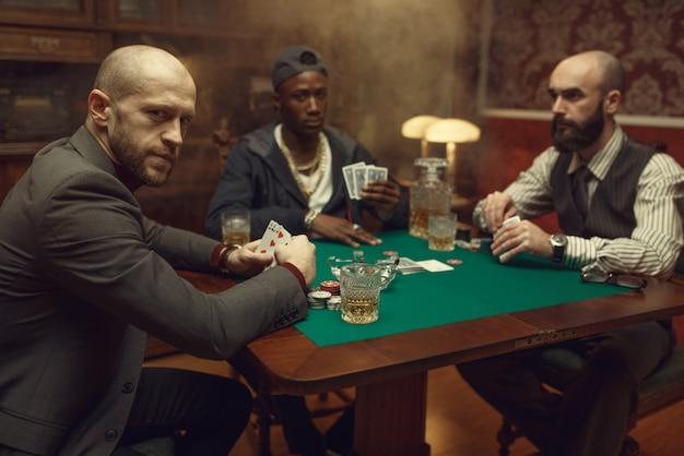 Giocatori di poker con carte che giocano nel casinò. giochi d'azzardo dipendenza, casa da gioco. svaghi maschili con whisky e sigari