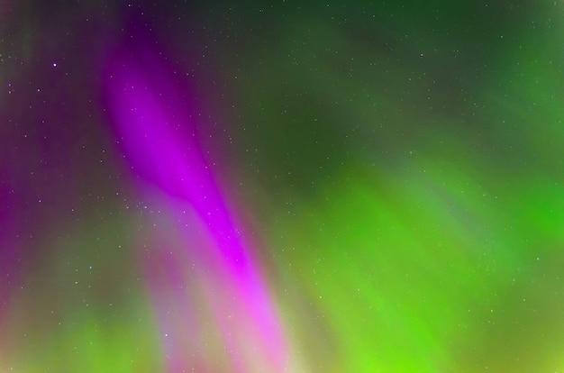 Luci polari aurora boreale nel cielo stellato notturno, consistenza e fenomeni naturali di colore viola e verde.