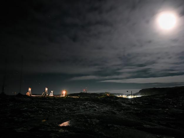 Stazione meteorologica polare sotto la luce della luna piena su una collina sulla riva del mare di barents