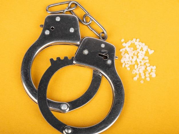 Braccialetti della polizia e manette antidroga e cristalli di anfetamine