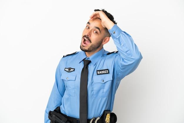 Uomo caucasico della polizia isolato su sfondo bianco che fa un gesto a sorpresa mentre guarda di lato