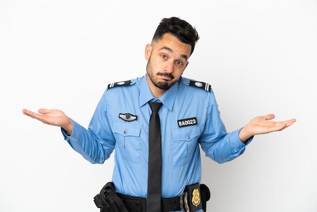 Uomo caucasico della polizia isolato su sfondo bianco che ha dubbi mentre alza le mani