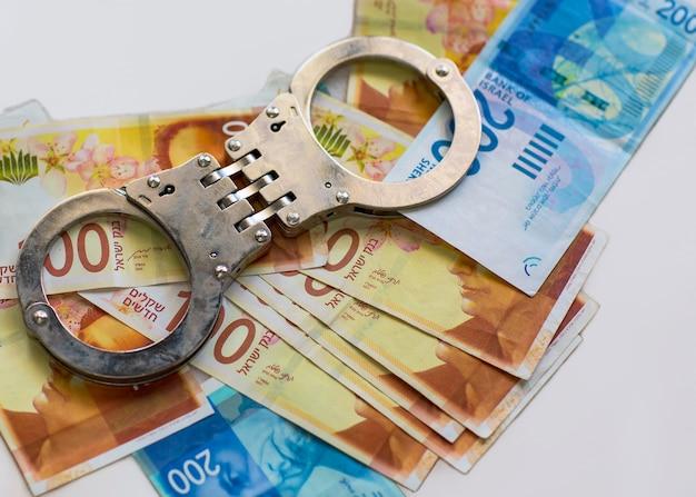 Manette della polizia sullo sfondo delle banconote del nuovo shekel israeliano sul tavolo