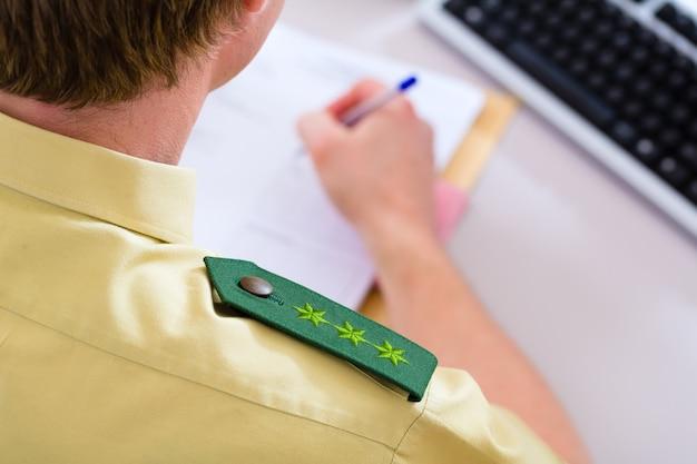 Agente di polizia nella stazione di polizia che lavora al computer, a un caso o registra una denuncia