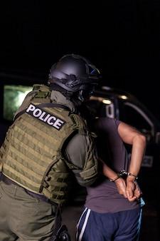 Un agente di polizia mette le manette sulle mani di un criminale durante un arresto. auto della polizia con fari lampeggianti. copia spazio