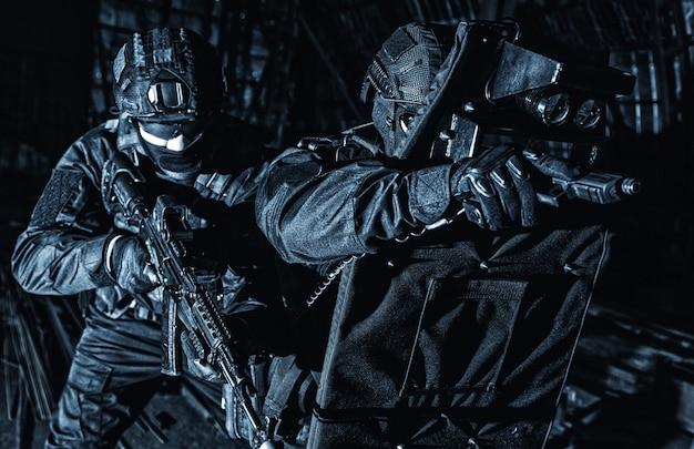 Combattenti di gruppo tattico per operazioni speciali di polizia in uniforme nera e maschera, pistola armata e fucile di servizio, proteggendosi con scudo balistico corazzato, furtivamente nell'oscurità durante il raid notturno