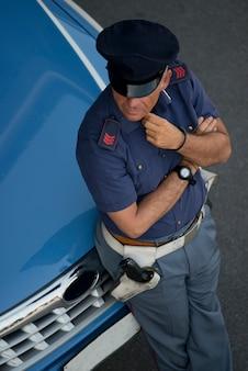 Poliziotto vicino alla sua macchina
