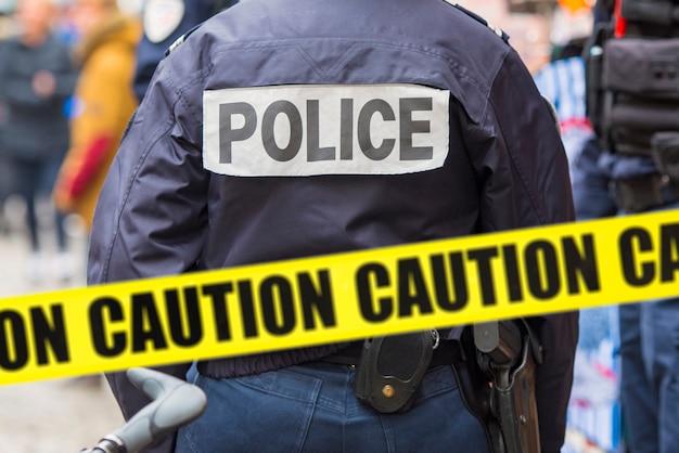 Poliziotto e nastro giallo sulla scena del crimine