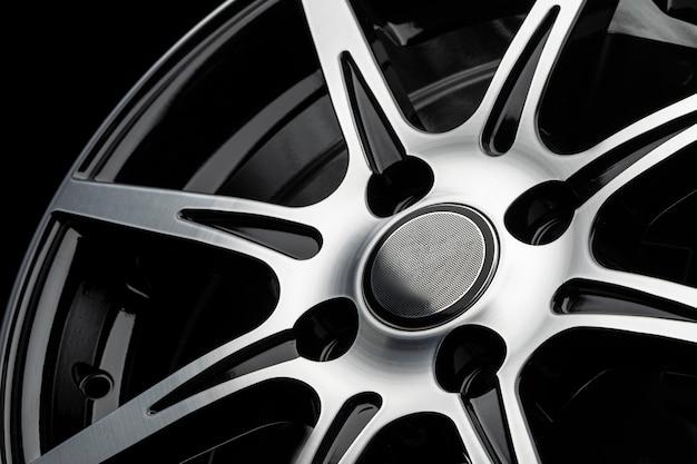 Raggi lucidati di una ruota in lega di auto, close-up su uno sfondo nero.