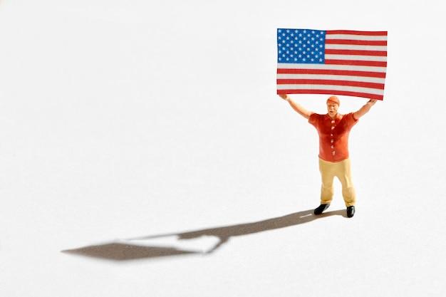 Figura di sostenitore politico con bandiera americana. miniatura di un uomo patriottico in camicia rossa, che tiene la bandiera degli stati uniti con entrambe le mani sopra la testa