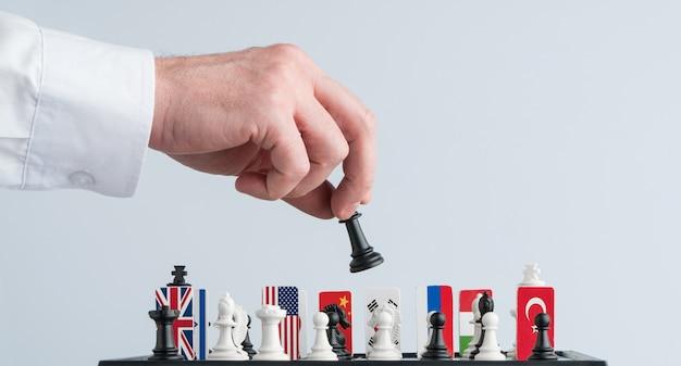 La mano del politico muove un pezzo degli scacchi. foto concettuale di un gioco politico e di una strategia.