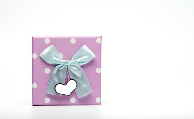 Contenitore di regalo punteggiato di polka con fiocco in nastro verde pallido e biglietto di auguri in bianco isolato su sfondo bianco con spazio di copia, basta aggiungere il tuo testo. utilizzare per il festival di natale e capodanno