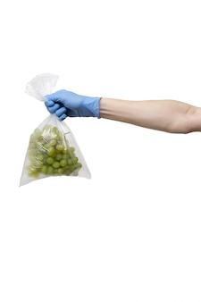 La borsa del politene dell'uva ha tenuto a disposizione i guanti blu d'uso sulla parete bianca