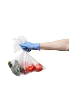 La borsa del politene delle verdure ha tenuto a disposizione i guanti blu d'uso sulla parete bianca