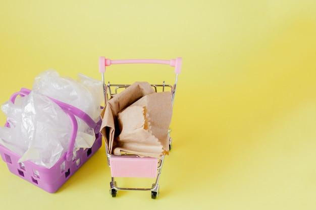 Politene e sacchi di carta in un cestino della spesa su un giallo