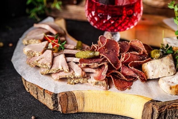 Bevanda alcolica al melograno con salsicce e carne stagionate assortite