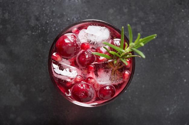 Cocktail di natale del melograno con rosmarino, champagne, soda del club sul nero. avvicinamento.