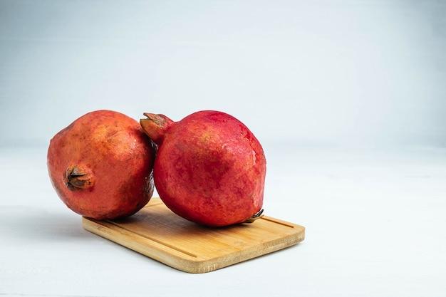 Frutta del melograno sui precedenti bianchi