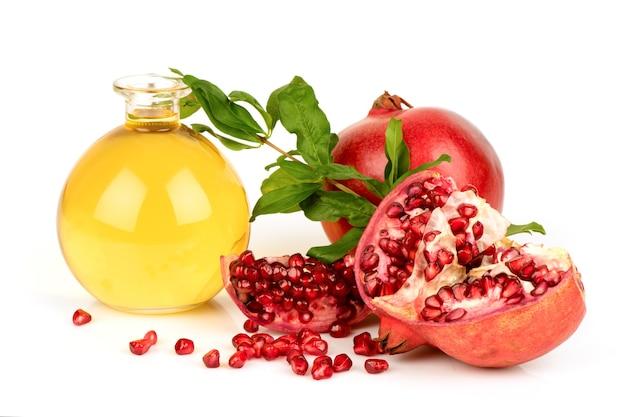 Frutti di melograno e olio isolati su sfondo bianco.