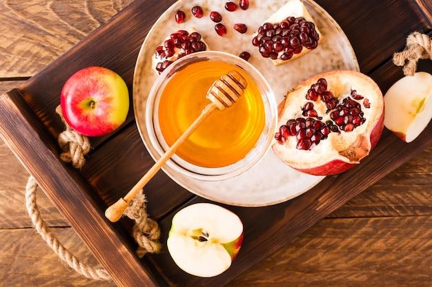 Melograno, semi di melograno e mele con miele per il rosh hashanah su un tavolo di legno, vista dall'alto.