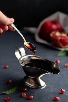 La salsa di melograno scorre giù da un cucchiaio in una salsiera sul buio