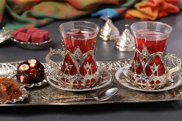 Tè al melograno e delizie turche sul vassoio di metallo su sfondo scuro