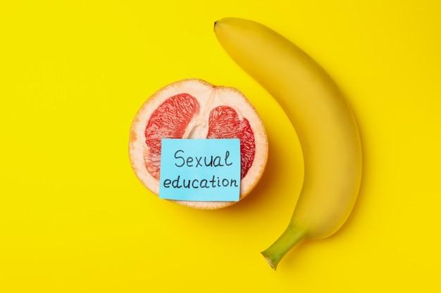 Pomelo con testo educazione sessuale e banana su sfondo giallo