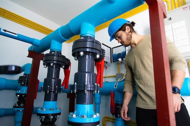Stanza del sistema di pulizia della piscina. servizio professionale e manutenzione della pompa dell'acqua della piscina. uomo del tecnico che lavora.