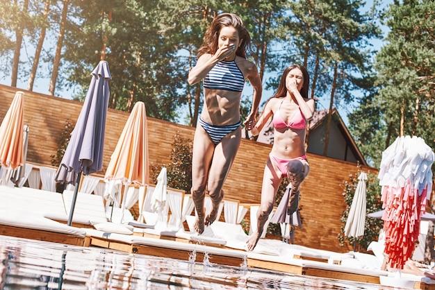 Tempo in piscina due belle e magre giovani donne in costume da bagno alla moda che saltano in piscina