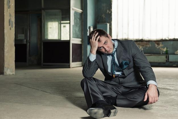 Povero uomo d'affari seduto sulla vecchia cantina