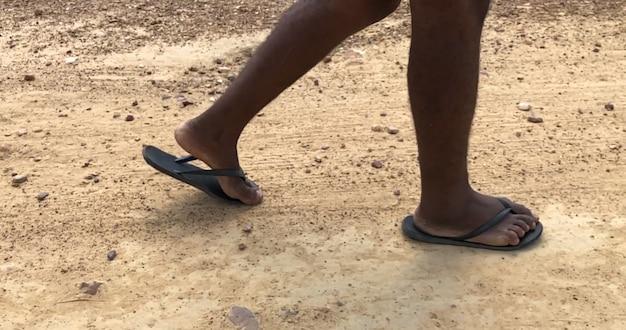 Piedi poveri del bambino che camminano su una strada sterrata in una calda giornata di sole.