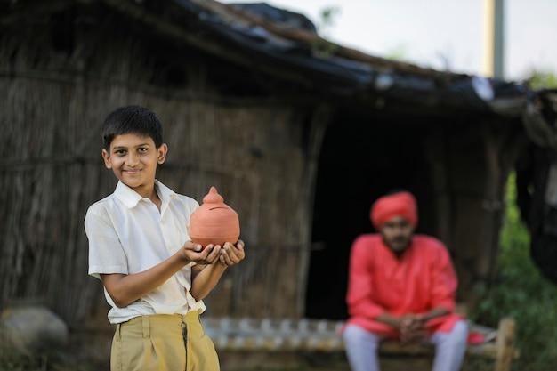 Bambino povero del coltivatore che tiene il porcellino salvadanaio dell'argilla in mano con il coltivatore a casa