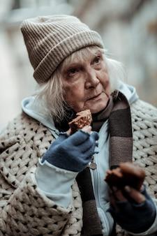 Povero e affamato. bella donna invecchiata che pensa alla sua vita mentre tiene un pezzo di pane